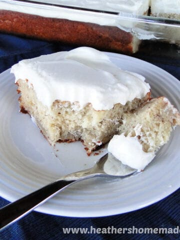 Slice of Banana Cake with Cream Cheese Frosting with a bite on a fork on white round plate.