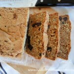 Top view of Chocolate Chip Zucchini Bread with 3 slices cut on bamboo board with bread knife on side of bread.