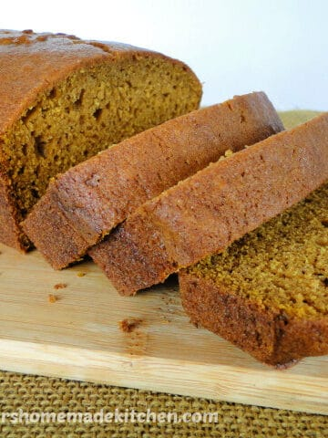 Side view of Easy Pumpkin Bread Recipe with 3 slices on board.