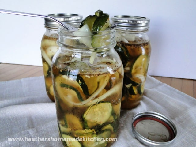 Easy Sweet Refrigerator Pickles in 3 mason jars with pickles on a fork in front jar.