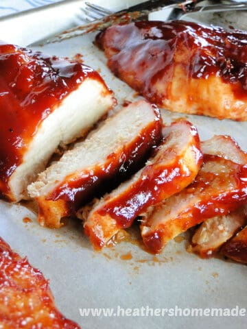 Oven Roasted BBQ Chicken breasts, sliced diagonally on sheet pan.