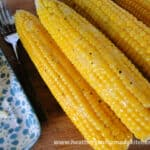 Easy Oven Roasted Corn with Husks, husks peeled and corn slathered with butter and sprinkled with cracked black pepper on a bamboo cutting board.