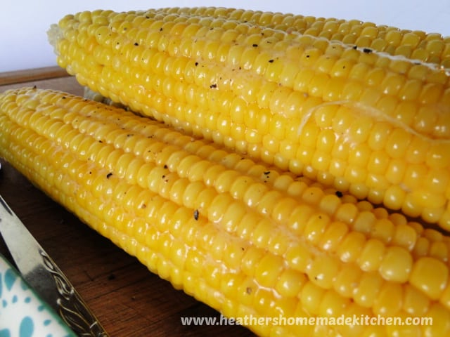 Oven Roasted Corn with Husks, husks peeled off, close view of 2 ears of corn with butter and cracked black pepper.