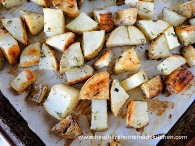 Diced Oven Roasted Potatoes on parchment paper on baking sheet.