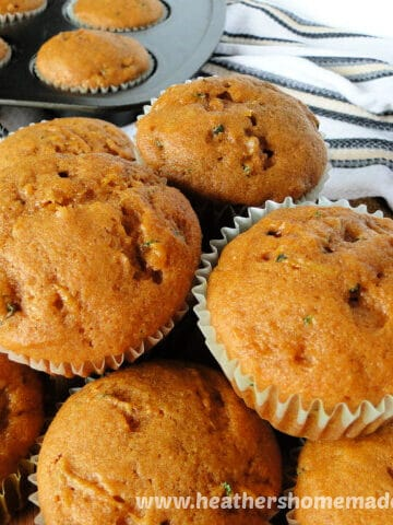 Side view of Pumpkin Zucchini Muffins piled on board.