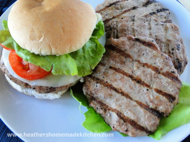 Turkey Burger with cheese, lettuce and tomato on bun with extra burgers on the side.