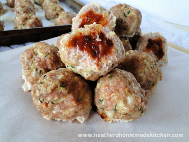 Turkey & Zucchini Meatballs in a pile with sheet pan of meatballs behind.
