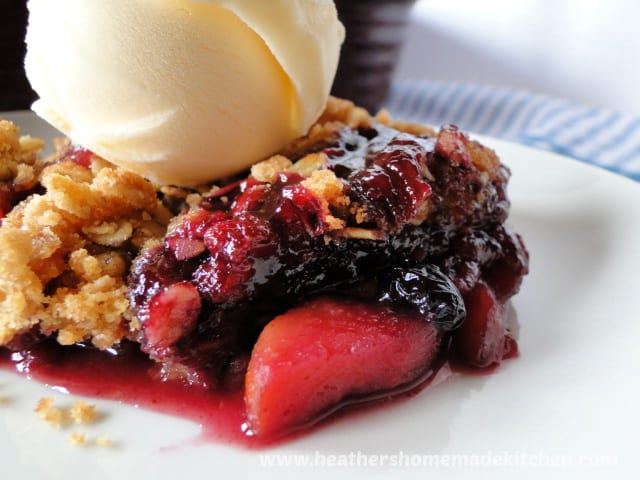Close up view of Very Berry Apple Crisp fruit and filling with scoop of vanilla ice cream.