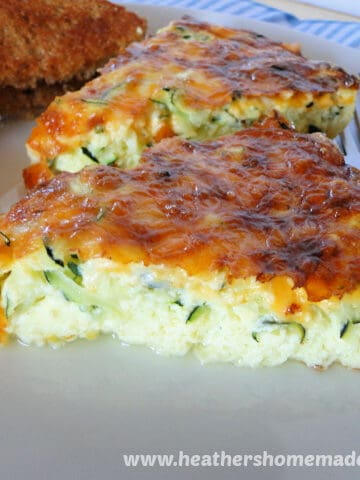 Side view of two slices of Zucchini Frittata on white plate with fork on right side and slice of toast on left side.