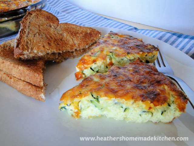 Two slices of Zucchini Frittata with toast on left side on white plate.