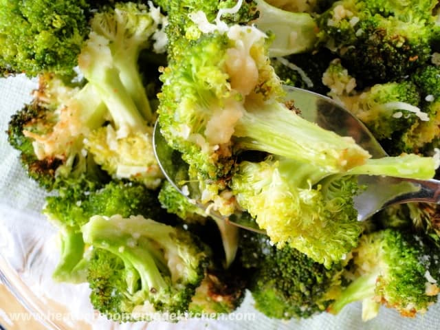 Air Fryer Garlic Parmesan Broccoli in glass bowl with florets on spoon.