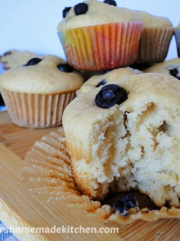 Close up view of Easy Blueberry Muffins on board with bite taken out of front muffin.