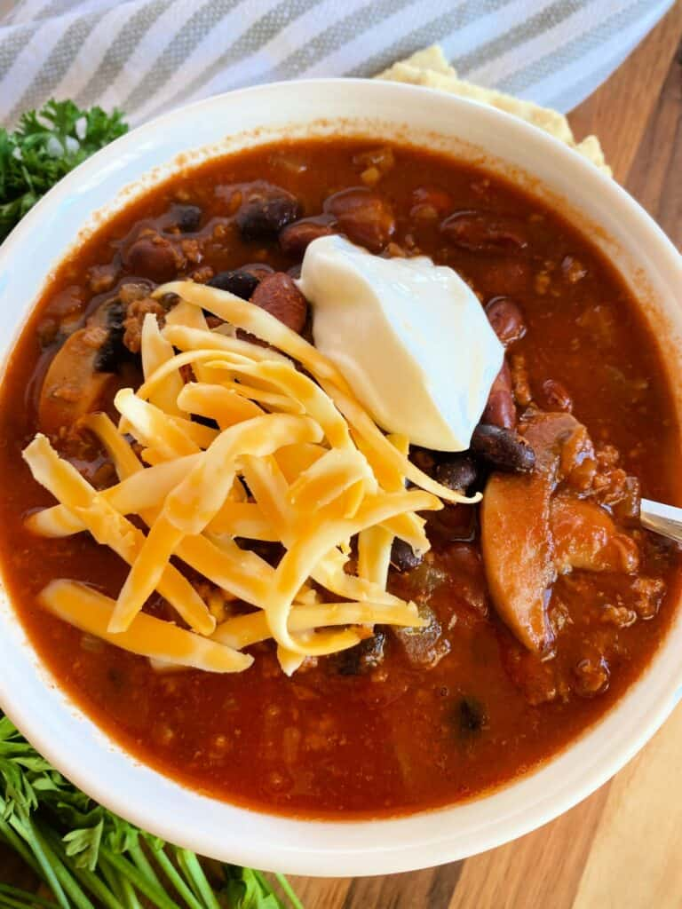 Top view of 3 bean chili in white bowl with spoon and topped with sour cream and yellow shredded cheese.
