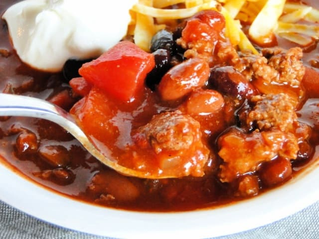 Close up view of spoonful of 3 bean chili.