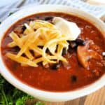 Side view of easy 3 bean chili in white bowl with spoon and topped with sour cream and shredded cheese.