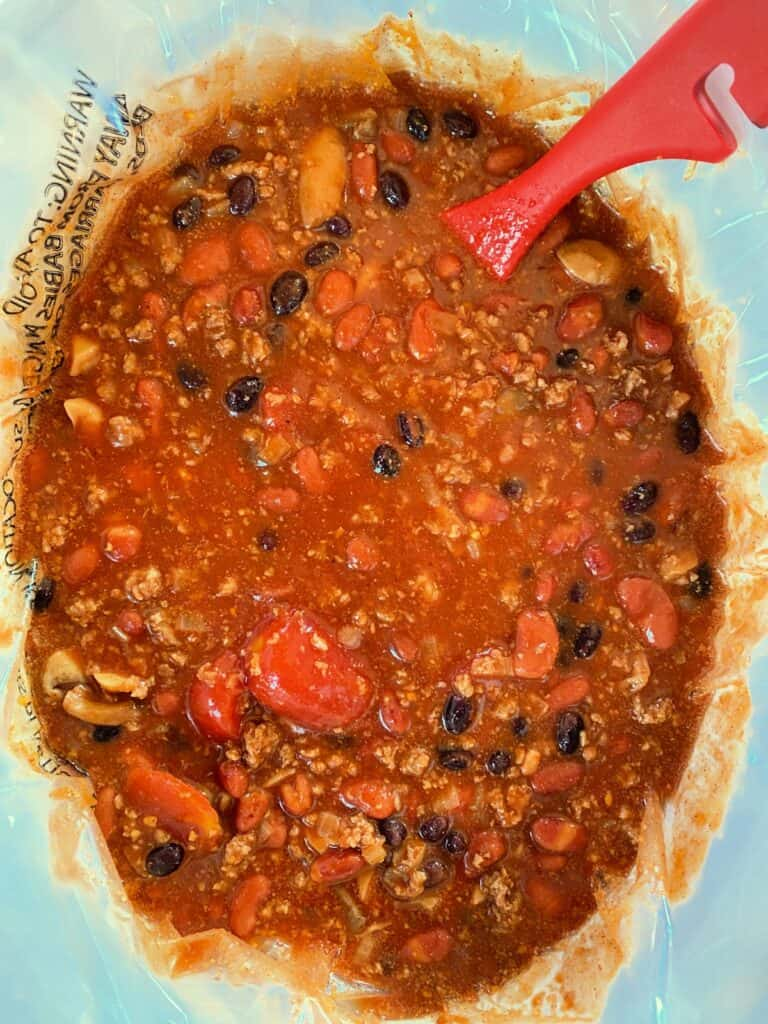 Cooked easy 3 bean chili in crock pot with red ladle.