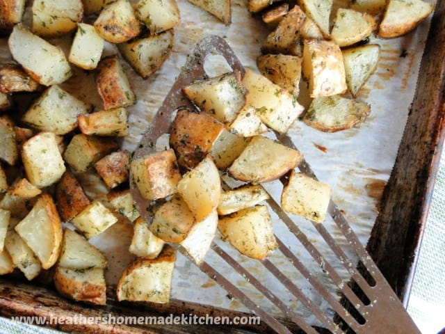 Top view of Roasted Ranch Potatoes on metal spatula in a sheet pan.
