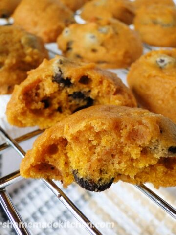 Soft Pumpkin Chocolate Chip Cookies in rows on wire rack with front cookie broken in half.