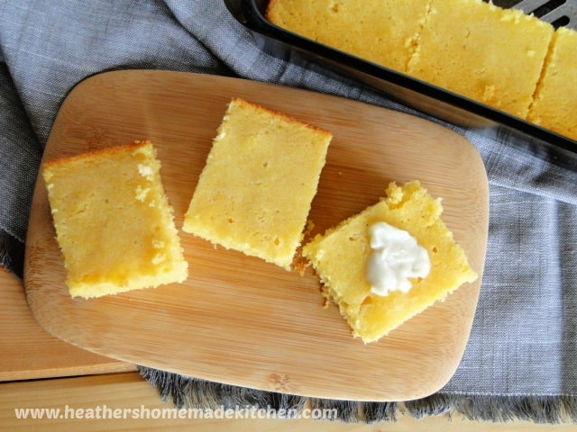 Top view of Sweet Cornbread Recipe slices on board with butter on top.