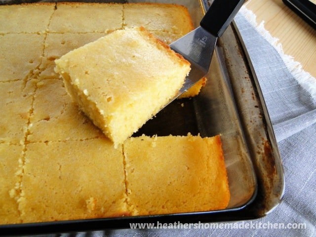 Sweet Cornbread Recipe sliced in glass baking dish with one piece on spatula.