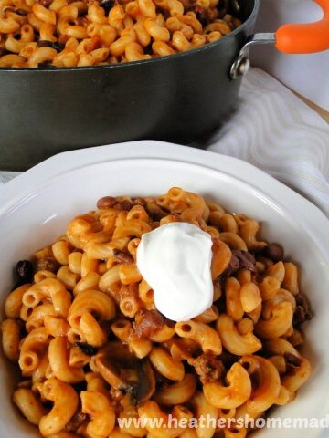 Chili Mac Skillet with Leftover Chili in white bowl with sour cream in front of skillet.