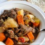 Crock Pot Beef Stew in white bowl with spoon and buttered bread on the side.