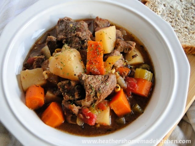Top view of Crock Pot Beef Stew in white bowl with buttered bread to the right side.