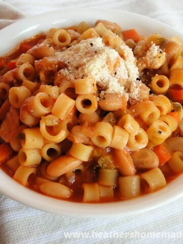 Pasta E Fagioli in white bowl with spoon and grated Parmesan cheese on top.