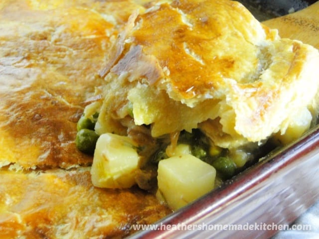 Close up view of Turkey Pot Pie with Puff Pastry scooped on wooden spoon.