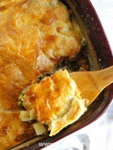 Turkey Pot Pie with Puff Pastry in burgandy baking dish with corner scooped on wooden spoon.