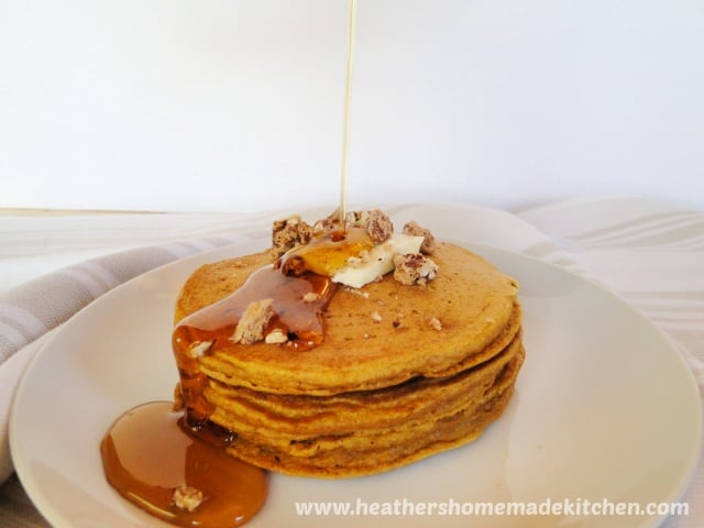 Whole Wheat Pumpkin Pancakes with maple syrup being drizzled on top.