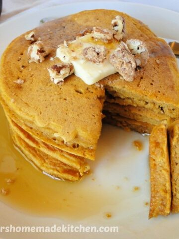 Whole Wheat Pumpkin Pancakes stacked on white plate with butter, pecans, maple syrup and a bite cut out and on fork.