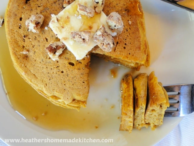 Top view of Whole Wheat Pumpkin Pancakes with butter, pecans and maple syrup.