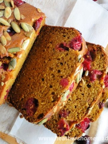 Top view of fresh cranberry pumpkin bread with slices on board and scattered fresh cranberries.
