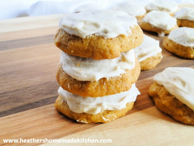 Stack of 3 Frosted Pumpkin Drop Cookies on board.