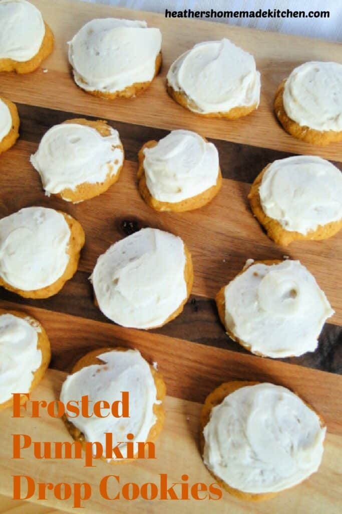 Frosted Pumpkin Drop Cookies in rows on wood board.