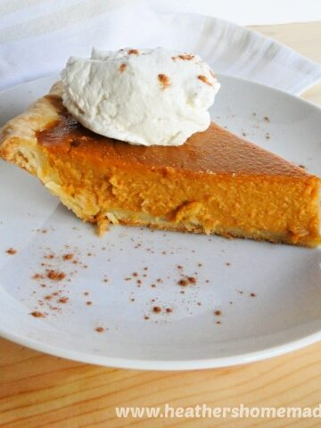 Side view of Homemade Pumpkin Pie Recipe with whipped cream and sprinkle of cinnamon on white round plate.