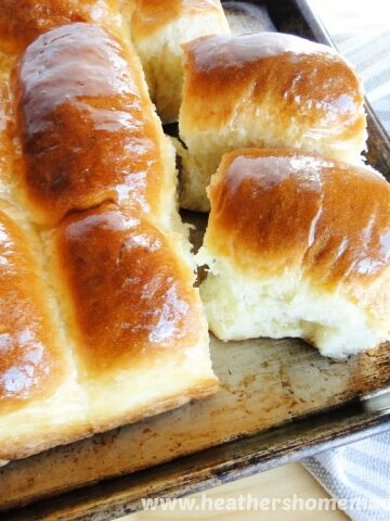 No Knead Dinner Rolls with rolls pulled apart on sheet pan.