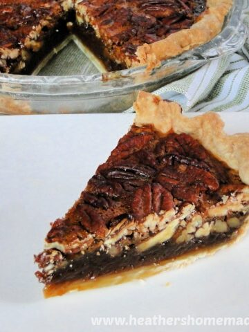 Slice of Homemade Pecan Pie Recipe on square white plate with whole pie behind plate.