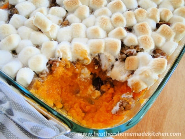 Sweet Potato Casserole in glass baking dish with corner scooped out.