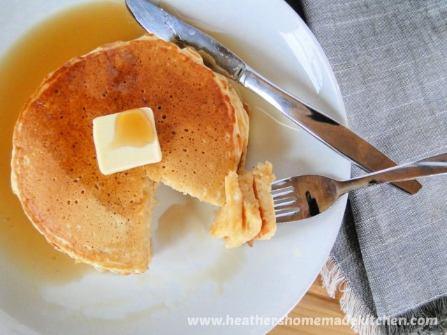 Homemade Buttermilk Pancakes with syrup and bite on fork.