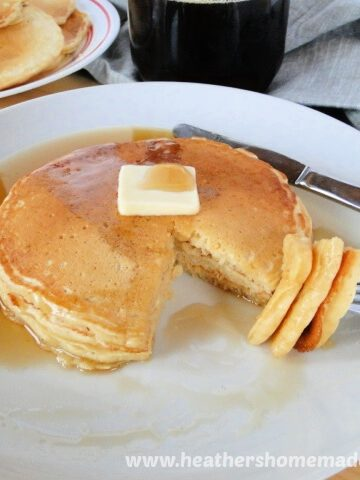 Homemade Buttermilk Pancakes stacked on white plate with butter, syrup and bite on fork.