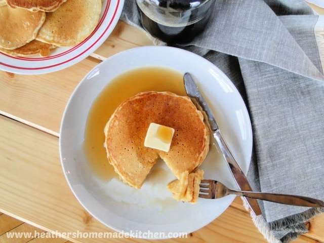 Top view of Homemade Buttermilk Pancakes on plate with butter, syrup and bite on fork.