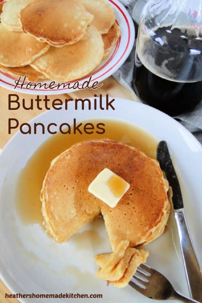 Homemade Buttermilk Pancakes stacked on white plate with pat of butter, maple syrup and bite on fork.