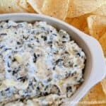 Crock Pot Spinach Artichoke Dip in oval baker with tortilla chips.