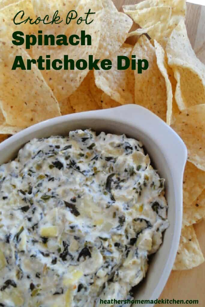 Crock Pot Spinach Artichoke Dip in oval dish surrounded by tortilla chips.