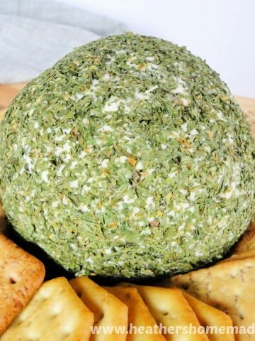Holiday Cheese Ball covered in green parsley surrounded by an assortment of crackers.