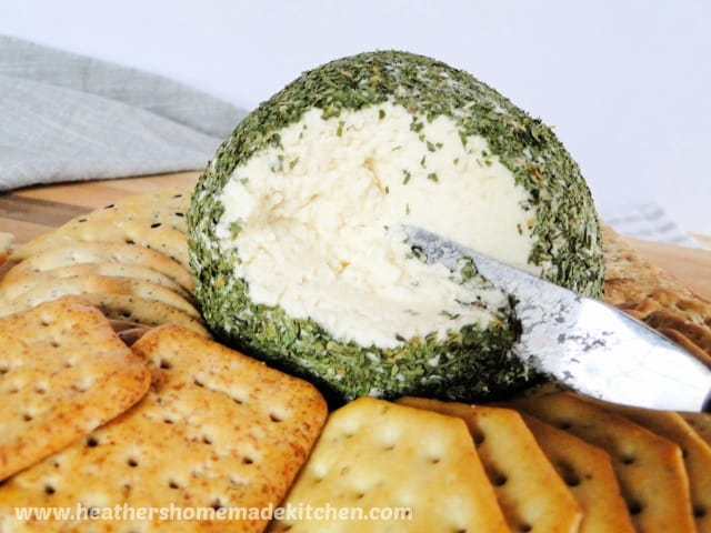 Holiday Cheese Ball in middle of crackers with side carved out using cheese spreader.