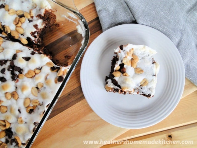 Slice of Rocky Road Brownies on plate next to baking dish of remaining.