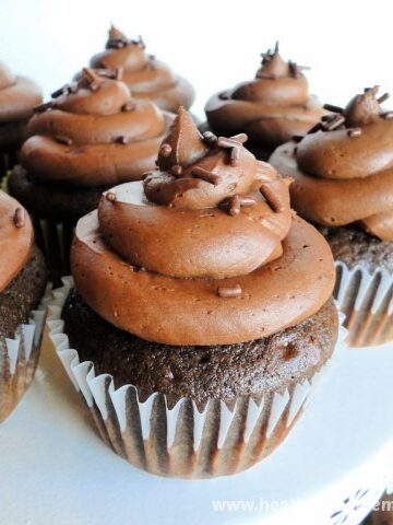 Homemade Chocolate Cupcakes with chocolate buttercream frosting and chocolate sprinkles on round white cake stand.